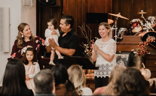 Family dedicating their daughter and Pastor Brynn